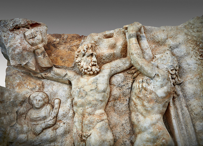 Close up of a Roman Sebasteion relief sculpture of Zeus and Prometheus, Aphrodisias Museum, Aphrodisias, Turkey.  <br /> <br /> Prometheus is screaming in pain. Zeus had given him a terrible punishment for giving fire to man: he was tied to the Caucasus mountains and had his liver picked out daily by an eagle. Herakles shot the eagle and is undoing the first manacle. He wears his trade mark lion-skin and thrown his club to one side. A small mountain nymph, holding a throwing stick appears amongst the rocks.