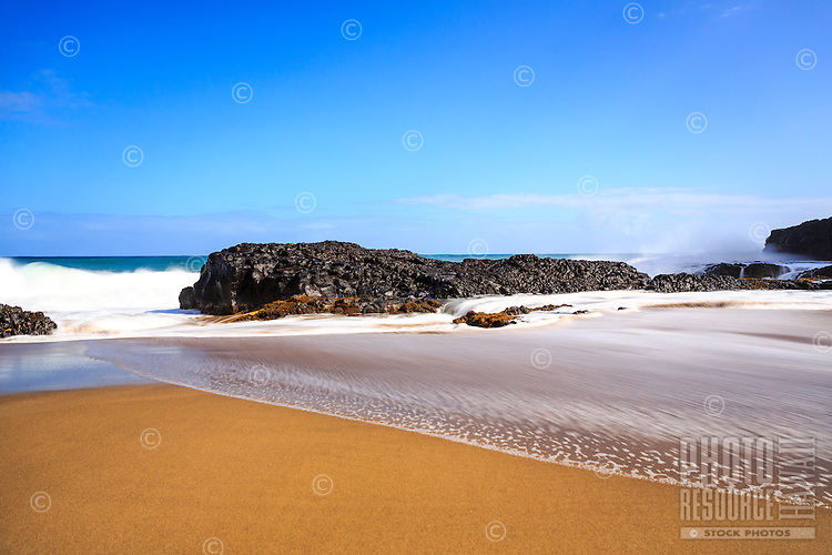 A wide beach runs into a rocky shelf of volcanic rock on a sunny afternoon at Lumaha'i Beach, Kaua'i.