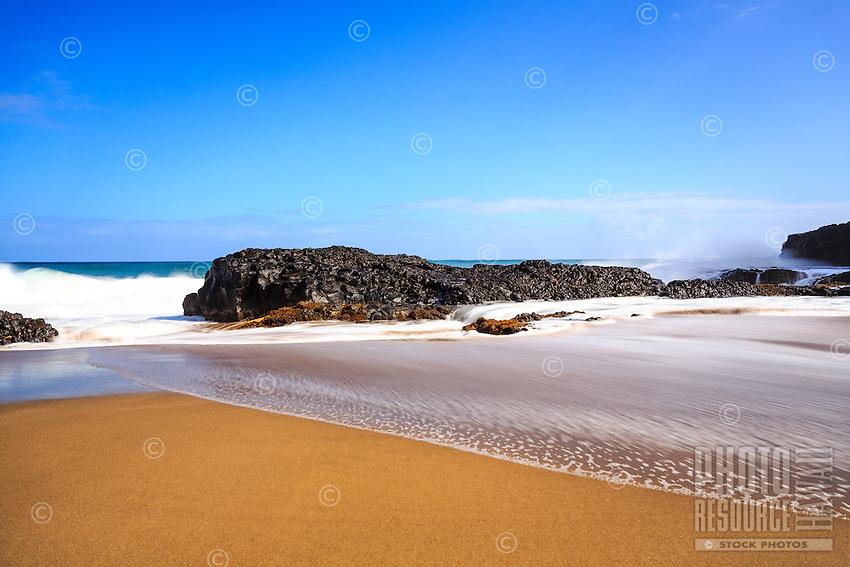 A wide beach runs into a rocky shelf of volcanic rock on a sunny afternoon at Lumaha'i Beach, Kaua'i.