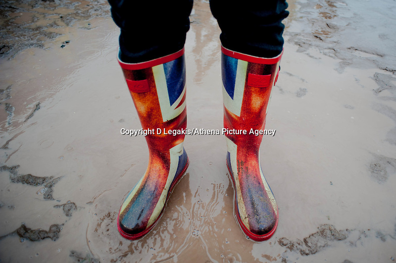 Thursday  29 May 2014, Hay on Wye, UK<br /> Pictured: A woman in union jack wells walks through the rain at the Hay festival, Hay on Wye, Powys, Wales UK.