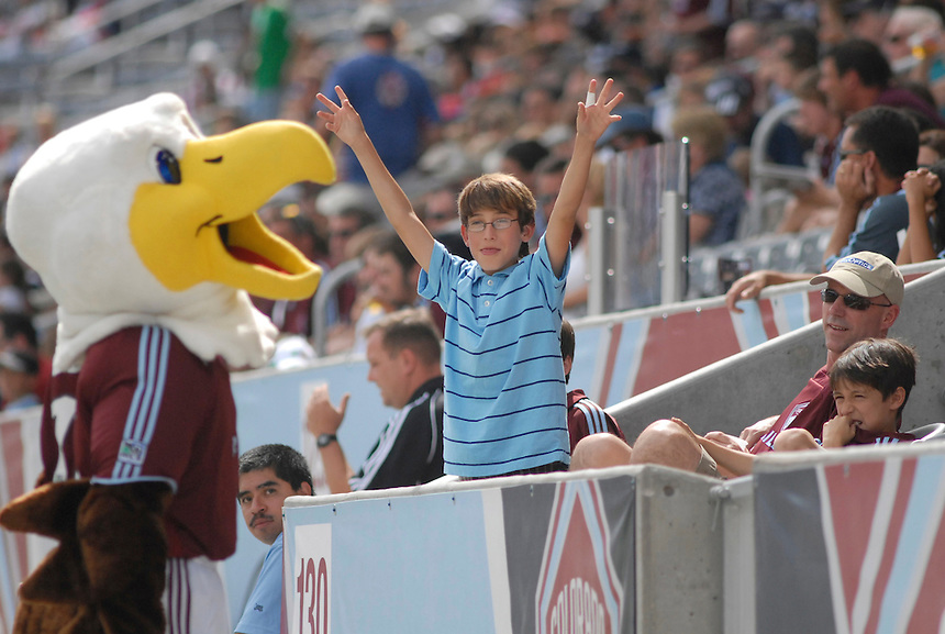A young fan tries to get the attention of the Colorado Rapids soccer club team mascot.