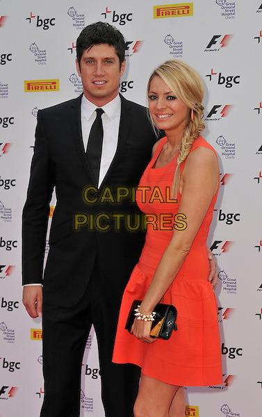 Vernon Kaye & Tess Daly.The F1 Party in aid of Great Ormond Street Hospital, Battersea Evolution, Battersea Park, London, England..4th July 2012.half length black suit white shirt tie orange dress clutch bag braid plait hair fishtail  sleeveless.CAP/WIZ.© Wizard/Capital Pictures.