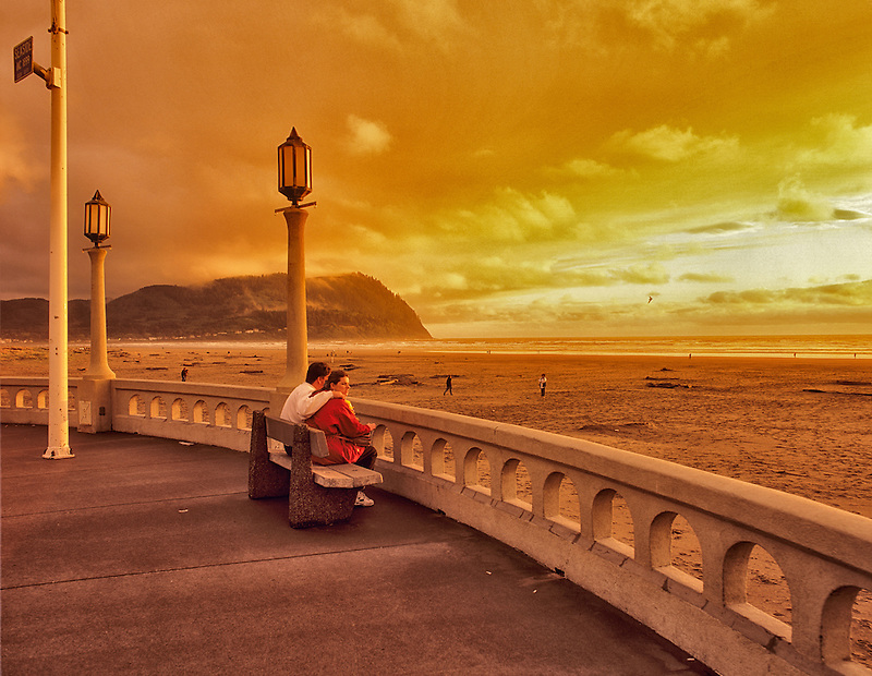 Couple on bench at Seaside beach at sunset. Oregon.
