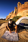 A young man camps in the Needles District of Canyonlands National Park, Utah (selective focus).