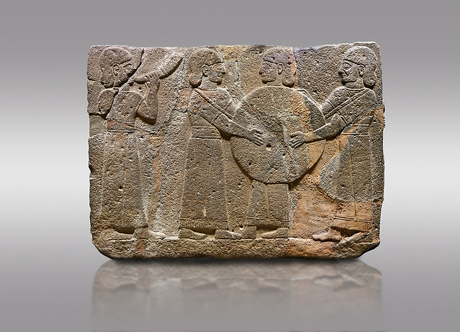 Picture & image of Hittite monumental relief sculpted orthostat stone panel of Procession. Basalt, Karkamıs, (Kargamıs), Carchemish (Karkemish), 900 - 700 B.C. Goddess Kubaba. Anatolian Civilisations Museum, Ankara, Turkey.<br /> <br /> Procession for. There are four figures on the other face of the orthostat. The leftmost figure plays a pipe, while the other three figures play the drums. All of the figures have long skirts and same body heights.  <br /> <br /> Against a gray background.