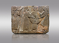 Picture &amp; image of Hittite monumental relief sculpted orthostat stone panel of Procession. Basalt, Karkamıs, (Kargamıs), Carchemish (Karkemish), 900 - 700 B.C. Goddess Kubaba. Anatolian Civilisations Museum, Ankara, Turkey.<br /> <br /> Procession for. There are four figures on the other face of the orthostat. The leftmost figure plays a pipe, while the other three figures play the drums. All of the figures have long skirts and same body heights.  <br /> <br /> Against a gray background.
