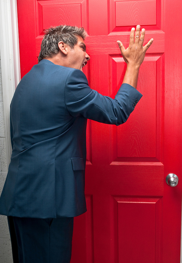 Very upset businesmman knocking off a door trying to collect a debt.