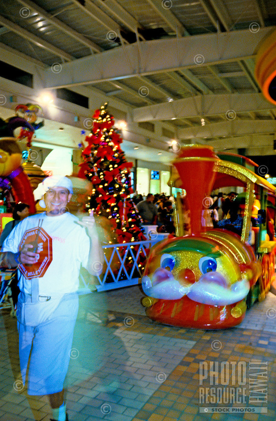 Local man dressed as Santa's elf displaying shaka sign in front of the annual holiday train at Ala Moana Shopping Center.