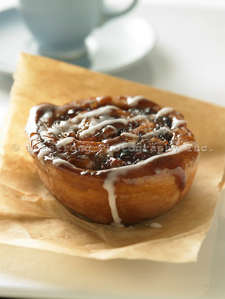 Sticky bun, with nuts, and dried fruit, and topped with icing.