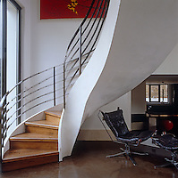 A leather swivel chair and matching footrest have been placed below a sleek curved staircase