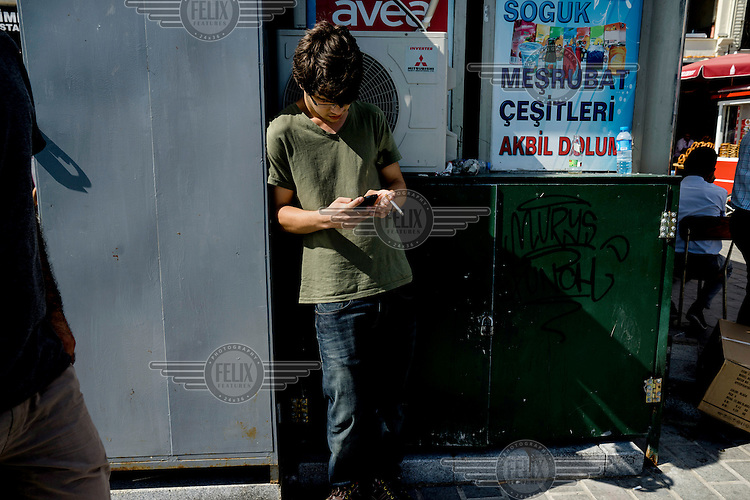 A young man smokes a cigarette while using a mobile phone in the Karakoy district.