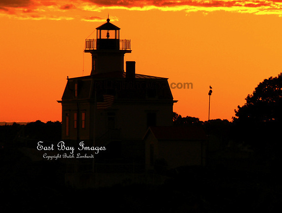The setting sun lights the sky on fire over Pomham Rocks Lighthouse.