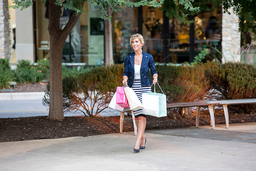 Attractive female shopper walks in the courtyard at beautiful Austin outdoor shopping mall