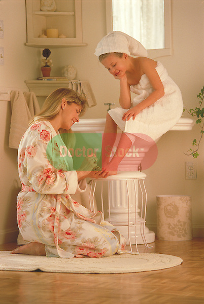 mother helping daughter with foot care in bathroom