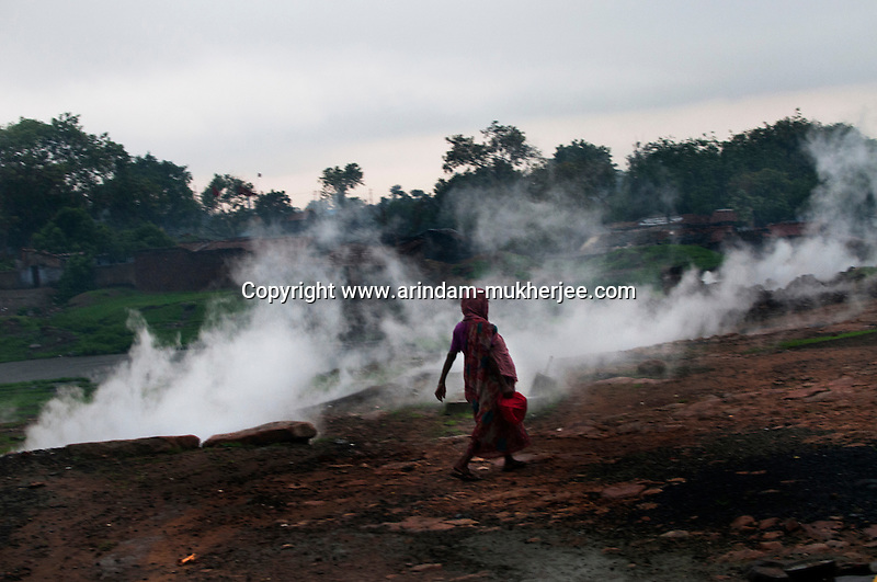 A woman walks past the poisonous gas and fumes caused by the burning coal seams beneath the surface. A huge coal mine fire is engulfing the city of Jharia from all its sides. All scientific efforts have gone in vain to stop this raging fire. This fire is affecting lives of people living in and around Jharia. Jharkhand, India. Arindam Mukherjee.