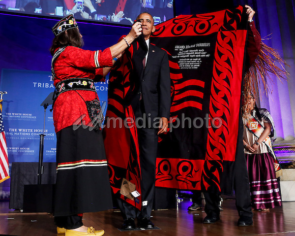 US President Barack Obama receives a traditional blanket and hat during the 2016 White House Tribal Nations Conference at the Andrew W. Mellon Auditorium, September 26, 2016, Washington, DC.  <br /> The conference provides tribal leaders with opportunity to interact directly with federal government officials and members of the White House Council on Native American Affairs. Photo Credit: Aude Guerrucci/CNP/AdMedia