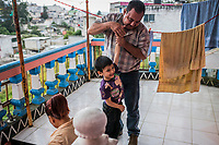 Carlos Saldana plays with Vicky's grandson Adolfo, as Vicky Delgadillo walks down from the balcony as they attend a birthday party for Vicky's  grandson, Hector Yael, 10, at a family gathering at Vicky's daughter, Cinthia Hernández Delgadilo's house in Xalapa, Mexico on November 4, 2017. <br /> Photo Daniel Berehulak for The New York Times