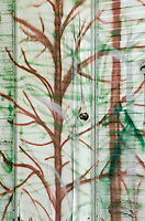Tree patterns are painted on the side of a abandoned motor home in a junkyard and hide the entrance which is noticeable mostly due to a door knob, Door County, Wisconsin