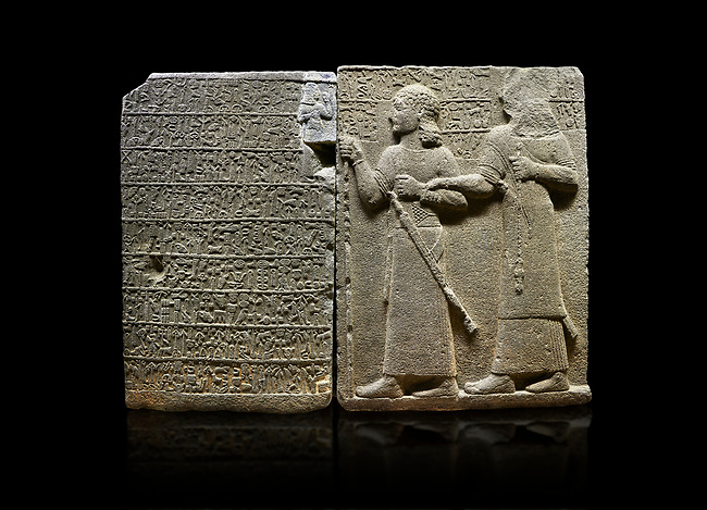 "Hittite monumental relief sculpted orthostat stone panel of Royal Buttress. Basalt, Karkamıs, (Kargamıs), Carchemish (Karkemish), 900-700 B.C. Anatolian Civilisations Museum, Ankara, Turkey.<br /> <br /> Hieroglyph panel (left) - Discourse of Yariris. Yariris presents his predecessor, the eldest son Kamanis, to his people. <br /> Right Panel - King Araras holds his son Kamanis from the wrist. King carries a sceptre in his hand and a sword at his waist while the prince leans on a stick and carries a sword on his shoulder. <br /> <br /> Hieroglyphs reads; ""This is Kamanis and his siblings.) held his hand and despite the fact that he is a child, I located him on the temple. This is Yariris' image"".  <br /> <br /> Against a black background."