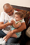 13 month old baby girl at home with father who is her primary caregiver feeding her bottle vertical