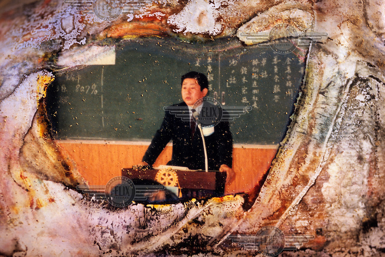 A damaged photograph of a man giving a speech or lecture.. It was found in an album lying by a roadside in Rikuzentakata, a city in Iwate that was devastated by the 11 March 2011 tsunami. Thousands of photographs, slowly deteriorating due to the elements, lie scattered throughout the tsunami affected region of Japan. The tsunami was triggered by a magnitude 9 earthquake that struck 130 km off the coast of Northern Japan and swept across the coast of Northern Honshu destroying all in its path.