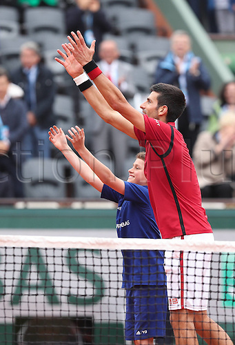 01.06.2016. Roland Garros, Paris, France, French Open tennis championships, day 11.  Novak Djokovic (R) of Serbia greets the fans with a ball boy after winning the mens singles fourth round match with Roberto Bautista Agut of Spain
