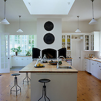 The contemporary kitchen contains a traditional pizza oven and iron drafting stools around a central work unit