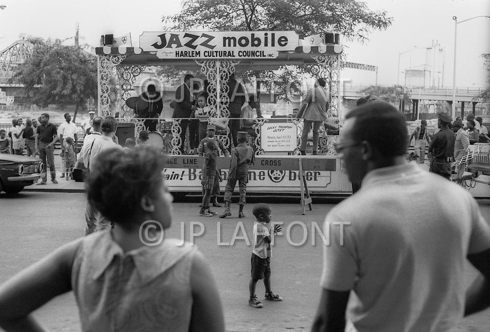 New York City, Harlem, Juillet 1966: Trois jeunes suivent avec enthousiasme le programe: Jazz Mobile qui a ete abandonne depuis. C'etait un camion qui parcourait lentement les rue d'Harlem l'été pour apporter un peu de joie sur les trottoirs!