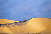 Fortaleza, Brazil. Sand dunes at Praia do Cumbuco with three people walking in front of them.