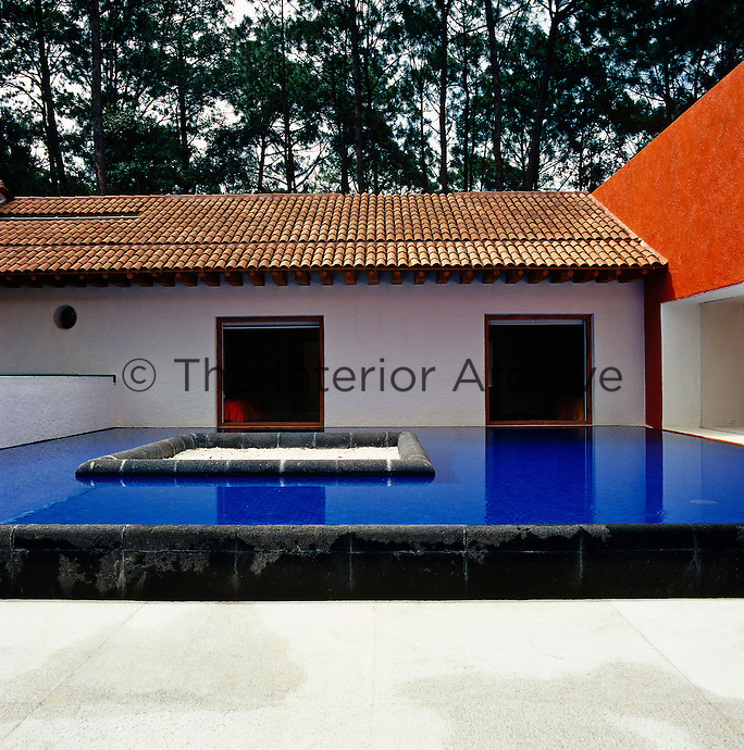 The central courtyard is dominated by a dark blue swimming pool