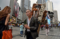59 year old former farmer Liu Yong ekes out a living in the city selling chicken-feather brushes in the centre of Chongqing city in southwestern China. He earns around 1,000 yuan a month selling these products, made of feathers he collects from chicken farms. His village was razed down several years ago by the government and has since lived in resettlement housing on the edge of the metropolis. The Chinese government plans to move 250 million rural residents into urban areas over the coming dozen years though it is unclear whether people want to move and where the money for this project will come from. Further urbanisation is meant to drive up consumption to counterbalance an export orientated economy and end subsistence farming but the drive to get people off the land is causing tens of thousands of protests each year. /Felix Features