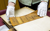 NWA Democrat-Gazette/JASON IVESTER --03/31/2015--<br /> Carolyn Reno, collections manager, displays the spine of a mid-1800's Bible on Tuesday, March 31, 2015, inside the Shiloh Museum of Ozark History in Springdale.