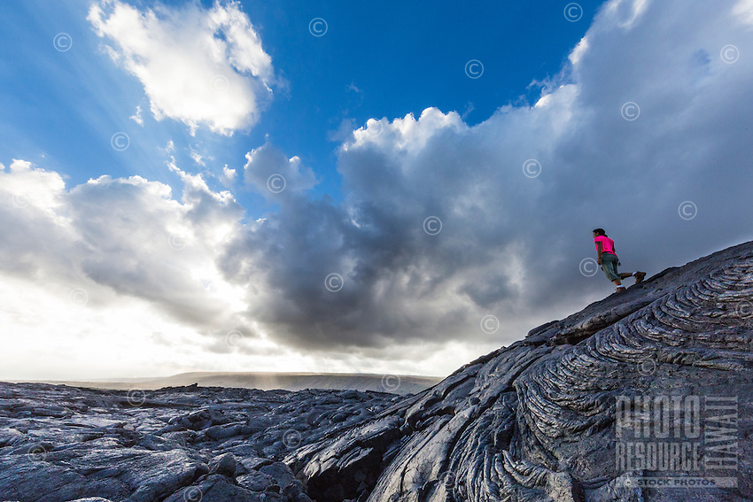 A woman hikes over the old lava fields of (Hawai'i) Volcanoes National Park to see the lava flow, Hawai'i Island.