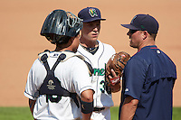 Cedar Rapids Kernels pitching coach J.P. Martinez (jacket) talks with starting pitcher Cody Stashak (30) and catcher Rainis Silva (18) during a game against the Dayton Dragons on July 24, 2016 at Perfect Game Field in Cedar Rapids, Iowa.  Cedar Rapids defeated Dayton 10-6.  (Mike Janes/Four Seam Images)