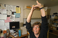 Karen Revill takes a quick break from office work to demonstrate some of the stretches she tries to do as often as possible at her desk at the Fuller Street Office Building at the University of Michigan in Ann Arbor on Friday, October 6, 2006. Four years ago, Revill developed carpel tunnel syndrome in her wrist. Though a recent surgery has cured most of her symptoms, she tries to remain active at work by taking several breaks throughout the day to stretch and walk around the office. &quot;I'm not as good as I should and I could be, but I'm trying to do more,&quot; Revill said.&amp;#xA;photo by Danny Gawlowski<br />