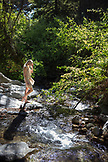 USA, California, Big Sur, Esalen, a woman walks down to Hot Springs Creek at the Esalen Institute