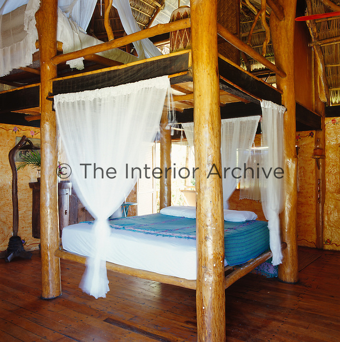 The bedroom has two beds built with the same rudimentary wooden structure; one on a mezzanine level above the other