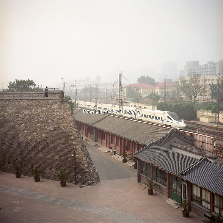 A Chinese high speed train passes a traditional building at the remnants of the Beijing city wall, October 2011.