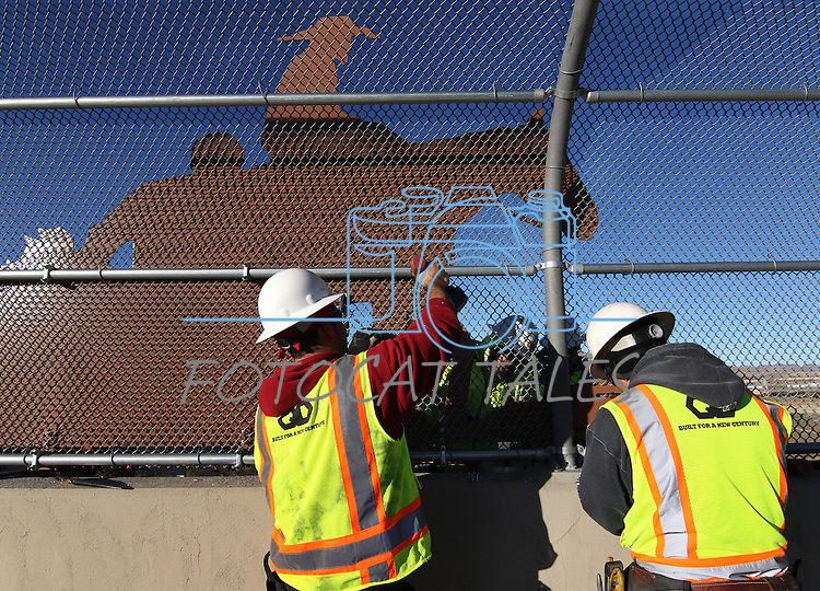 """Tony Ramirez, left, and Gabriel Delacerda, foreground, and Anthony Livengood and Mike Jennings with Q&D Construction, install """"cattle drive image panels"""" on the Fairview overpass above the Highway 395 bypass on Monday afternoon in Carson City..Photo by Cathleen Allison"""