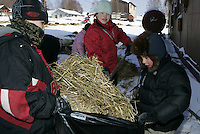 Laura Fox, Walter Sobba and CJ Fox help clean up dog straw Wednesday at the Takotna checkpoint