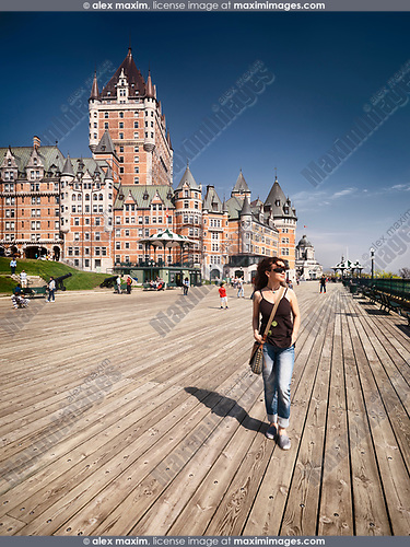 Young woman walking alone on Dufferin terrace boarwalk with Fairmont Le Château Frontenac castle in the background, luxury grand hotel Chateau Frontenac, National Historic Site of Canada. Old Quebec City, Quebec, Canada. Terrasse Dufferin, Ville de Québec.