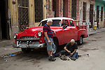 HAVANA, CUBA -- MARCH 24, 2015:   A mechanic works underneath a classic car in Havana, Cuba on March 24, 2015. Photograph by Michael Nagle