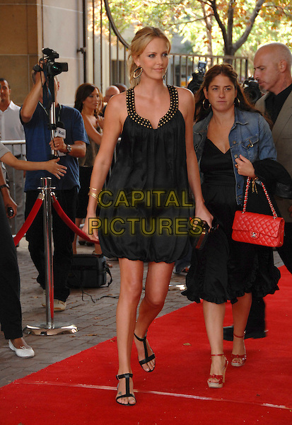 """CHARLIZE THERON.Arrives at The 32nd Annual Toronto International Film Festival for the """"Battle in Seattle"""" Premiere in Ryerson.Toronto, Ontario Canada, September 8, 2007..full length black dress gold studded collar ponytail earrings hoops flat sandals shoes .CAP/TL.©Tony Lee/Capital Pictures."""