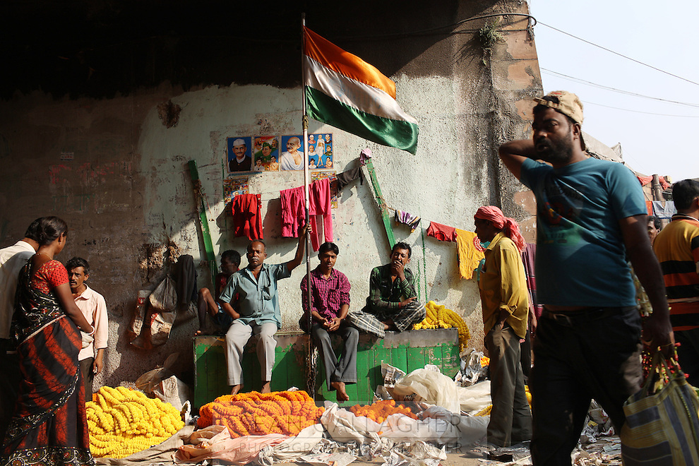 An Indian flag flies above a small market underneath the Howrah Bridge. November, 2013