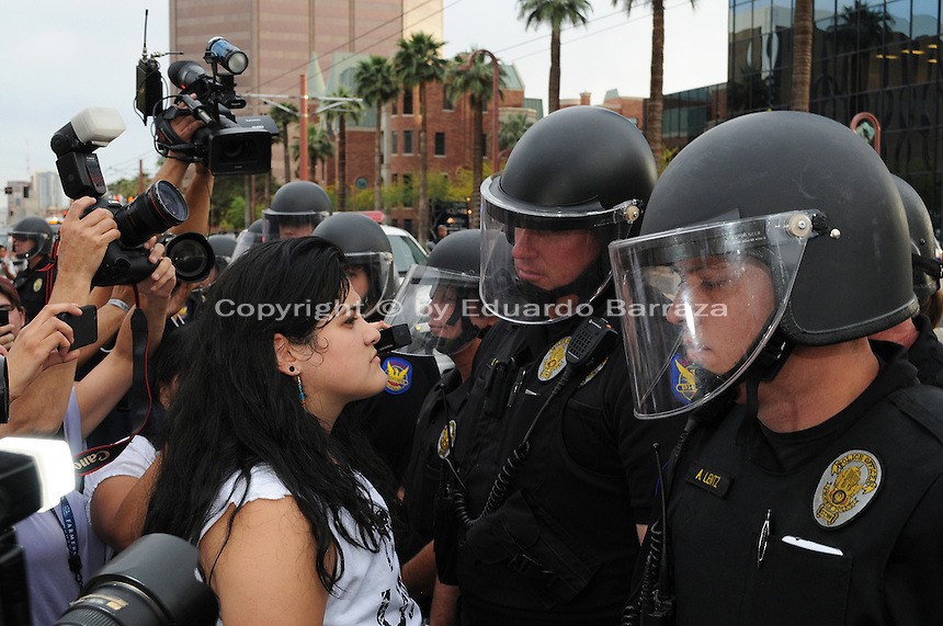 Phoenix, Arizona. April 25, 2012 - Demonstrator and activist Sandra Castro stands between media reporters and police officers as she blocks a section of Central Avenue in protest of SB 1070. About 500 people protested the controversial law on the same day U.S. Supreme Court justices heard legal arguments on the Arizona vs. United States case. At the end of the march, six activists blocked Central Avenue by sitting in the middle of the street. They all were arrested by the Phoenix Police Department and taken to the Fourth Avenue County Jail. Photo by Eduardo Barraza © 2012