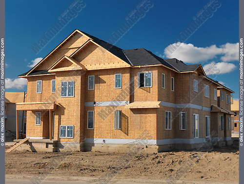 Wooden-frame two-story house with OSB sheathed walls under construction. Milton, Ontario, Canada.