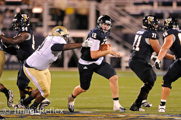 8 September 2012:  FIU quarterback Jake Medlock (12) attempts to evade Akron defensive lineman Mike Davis (79) in the third quarter as the FIU Golden Panthers defeated the Akron Zips, 41-38 (overtime), at FIU Stadium in Miami, Florida.