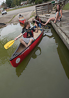 NWA Democrat-Gazette/J.T. WAMPLER Caroline Fox (right) helps Stephen Storment (left) and Marci Early shove off in a canoe Sunday Sept. 20, 2015 at Lake Fayetteville. The trio are part of the University of Arkansas civil engineer's concrete canoe team. They were at the lake to practice rowing for the 2016 National Concrete Canoe Competition.