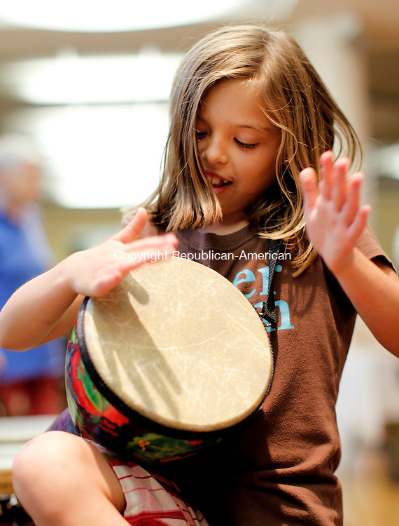 Litchfield, CT-14, July 2010-071410CM06  Kayla Bouchard, 7, of Litchfield bangs on a bongo drum Wednesday night at the Litchfield Community Center.  Bouchard was with friends attending the drumming which featured Master percussionist, John Marshall. Kids played games and enjoyed ice cream sundaes served by St. Anthony's Church.   --Christopher Massa Republican-American