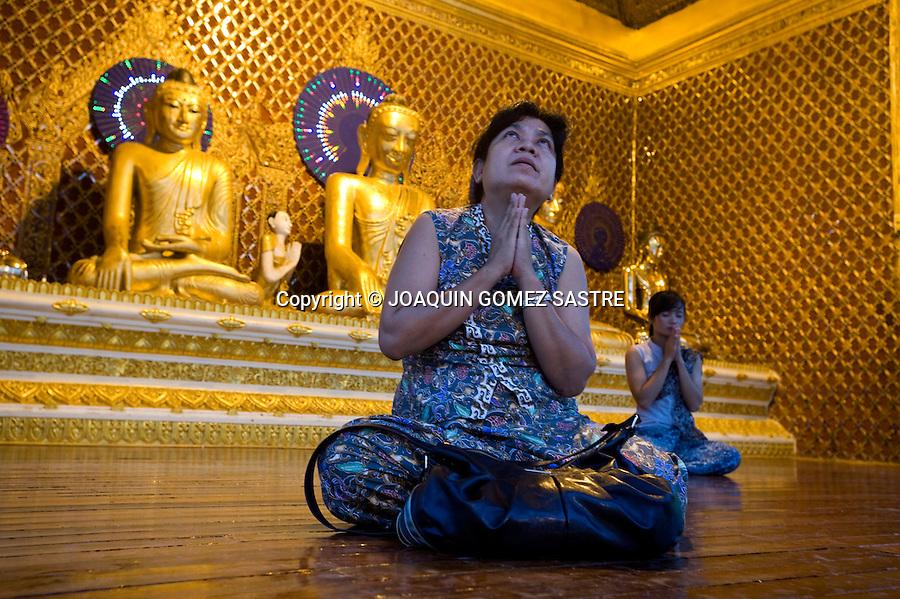 Mujeres rezando ante unas figuras de Buda en un templo de Myanmar.foto © JOAQUIN GOMEZ SASTRE
